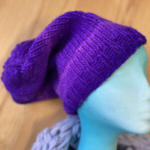 sie sehen eine gestrickte lila Mütze in legerer Form aus der ökozertifizierten Wolle von Atelier Zitron : einhundert, reine Schulwolle mit leichtem Farbverlauf